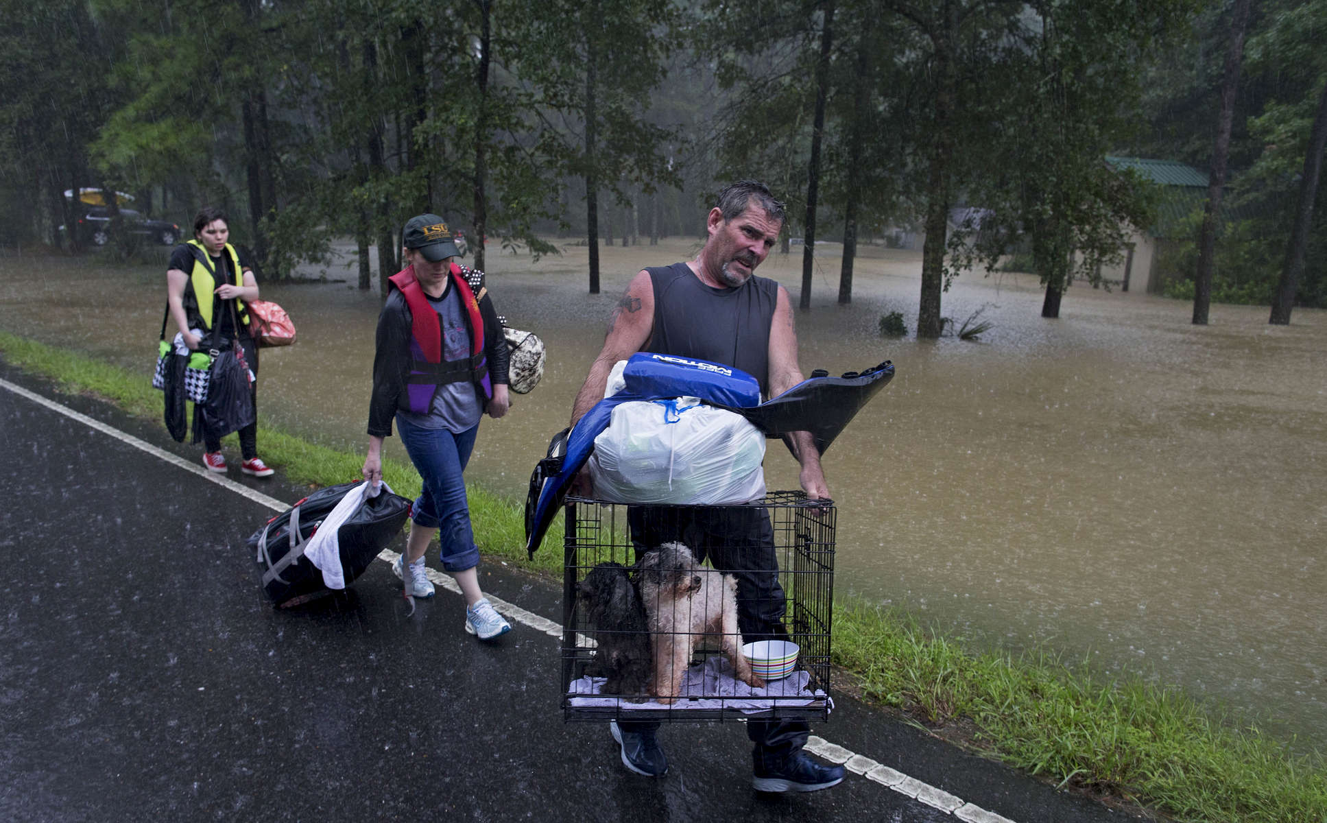 People arrive to be evacuated by members of the Louisiana Army National Guard near Walker, La. USA, in heavy rain, Sunday, Aug. 14, 2016. After Hurricane Katrina, Congress passed the Pets Evacuation and Transportation Standards Act compelling first responders to save pets just as they save people. Louisiana Gov. John Bel Edwards said the Louisiana National Guard rescued more than 1,000 people and hundreds of pets. (AP Photo/Max Becherer)