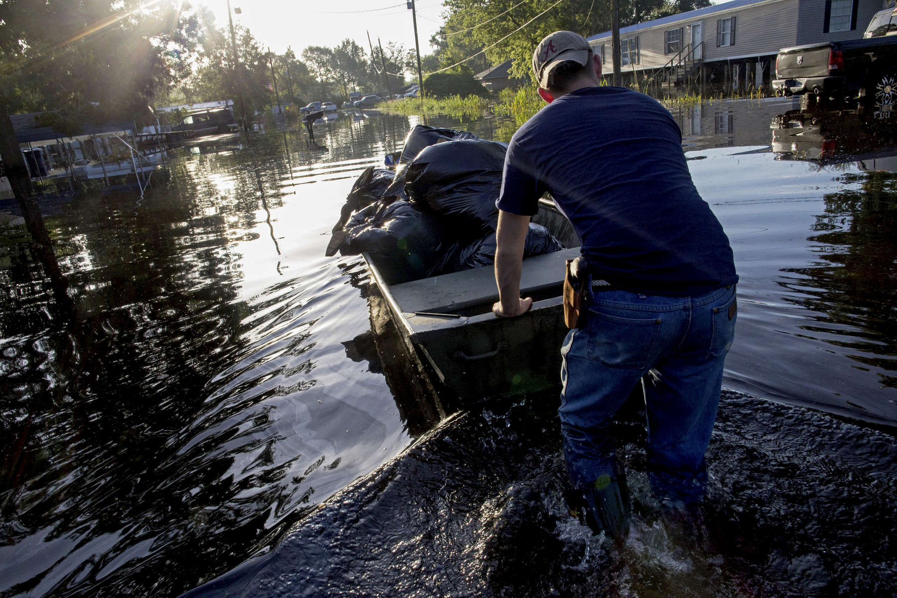 Daniel Stover, 17, moves a boat of personal belongings from a friend's flooded home in Sorrento, La. USA, Saturday, Aug. 20, 2016. The American Red Cross described the flood as {quote}the largest natural disaster to hit the United States since Superstorm Sandy.{quote} (AP Photo/Max Becherer)