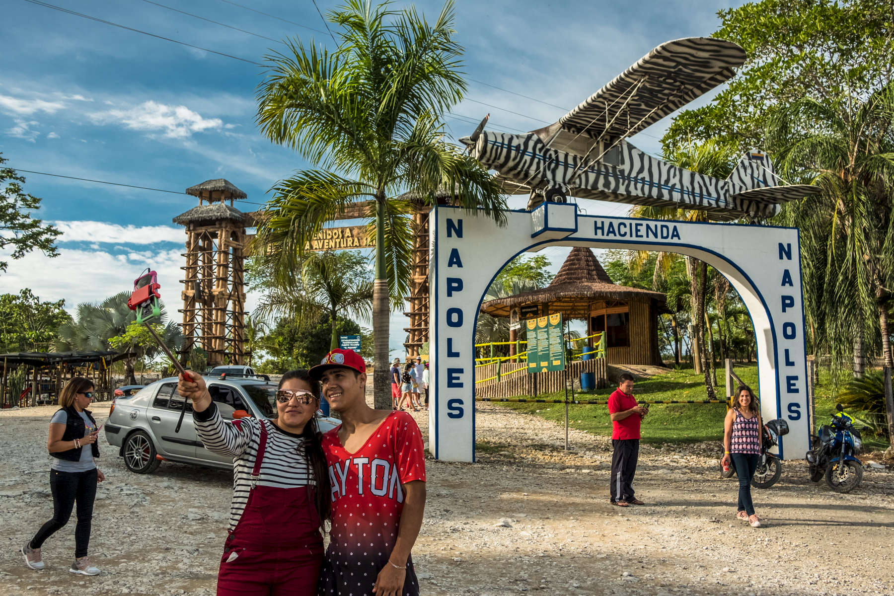 August 19, 2017. Puerto Triunfo, Antioquia, Colombia. Visitors take pictures at the old entrance of the Hacienda Napoles. The airplane on top it has been said to be a replica of the Piper PA-18 airplane which transported Escobar's first shipment of cocaine to the US. The luxurious 7.7 sq miles was build and owned by Pablo Escobar in the early 80's. After his death in 1993, the farmed was abandoned and raided. In 2006, the Colombian Government acquired the ownership of the property. In 2014, an African theme park was built. Parque Tematico Hacienda Napoles (57.018000520344, http://www.haciendanapoles.com/contactenos)