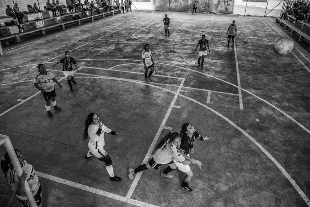 September 25, 2017. La Elvira, Cauca, Colombia. FARC women soccer team (black) play against the local village of La Esperanza at the transitional zone's indoor football court. After the peace agreement was signed between the Colombia Government and FARC in October of 2016. FARC members were divided into 26 transitional zones.  The women's soccer teams since April of 2017 have started to play game with local communities. Xiomara Mendez recalls that in times of combat they would play soccer in the middle of the jungle and two women were always included in the men's team but never had the opportunity to play all women's games.