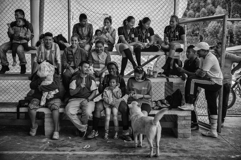 September 25, 2017. La Elvira, Cauca, Colombia. Some local residents from the nearby villages of Los Robles and El Cedral come to support their local teams, and members of the FARC women's soccer team and fellow comrades sit on the stands in between games. The women's soccer teams since April of 2017 have started to play game with local communities. Xiomara Mendez recalls that in times of combat they would play soccer in the middle of the jungle and two women were always included in the men's team but never had the opportunity to play all women's games.