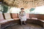 Author Sarah Wiseman sitting under her palapa in her garden.  Morelos, Mexico