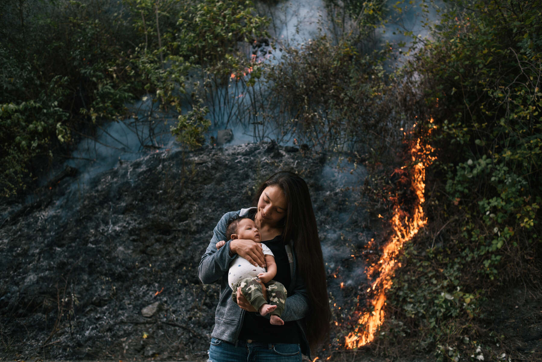 Crissy Robbins holds her son Kenneth Koy-o-woh during a prescribed cultural burn in Weitchpec, California. This twice-annual burn on Yurok land is part of a Cultural Fire Management Council training in which indigenous fire practitioners share traditional and modern knowledge with firefighters from around the world. In a recent survey, the Yurok community identified bringing fire back to the land as their top priority.For millennia, indigenous people in California and worldwide burned their land to promote food security, renew cultural and medicinal resources, create animal habitat and control larger fire risk—until colonizers made these methods illegal. Now increasingly devastating wildfires have government agencies reconsidering the use of prescribed burning as a preventative measure, and looking to traditional knowledge to guide some of their policies. Meanwhile, the Yurok and other tribes are working to revive their fire culture and reclaim their right to burn on sovereign land.