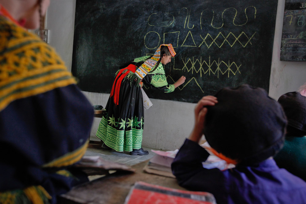 Teacher Noorzia Khan, 16, writes letters from the Kalasha alphabet on a blackboard during a lesson at the Kalasha Dur school and community centre in Brun village, located in the Bumboret Kalash valley on October 13, 2011. The Kalash, who number about 3,500 in Pakistan's population of 180 million, are spread over three valleys along the border with Afghanistan and are known for their distinctive dress, vibrant religious festivals, and polytheism. This tiny religious community claims descent from Alexander the Great's army, and say their unique culture is now threatened by a strict version of Islam promoted by increasingly relentless proselytisers, the impact of growing political instability and a shrinking local economy.