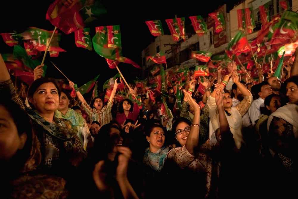 Pakistani supporters of Imran Khan, chairman of the Pakistan Tehreek-e-Insaf political party, wave flags and cheer during an election campaign rally in Lahore on May 2, 2013. Pakistan is holding parliamentary elections on May 11, the first transition between democratically elected governments in a country that has experienced three military coups and constant political instability since its creation in 1947.