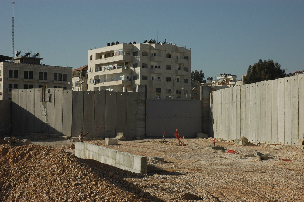 A Ram, a Jerusalem suburb, is separated from Jerusalem by a 26 ft concrete wall. It snakes in and out separating houses, and families.