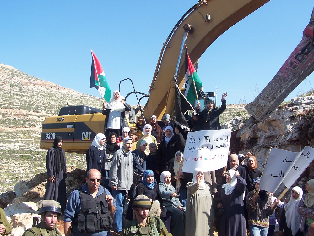 Women blocking the bulldozers from constructing the wall.