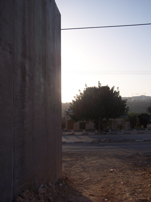 Bethlehem is enclosed by a 26 ft concrete wall. It snakes in and out separating houses, and families.