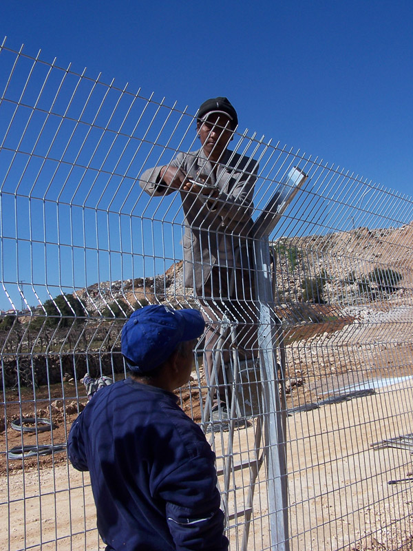 Migrant workers building the fence in Hebron