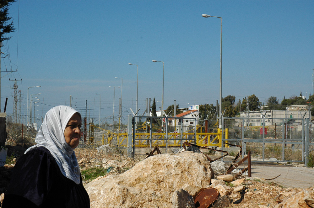 Mas'ha is enclosed by a separation fence, the other side an Israeli settlement in the West Bank.