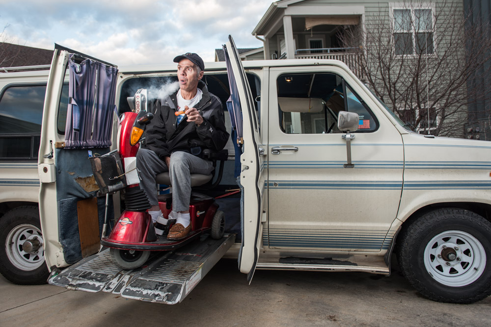 Charles Krushinski sits in his power wheelchair in front of his modified wheelchair van and smokes marijuana from a pipe.