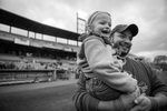 Sal Failla, Arianna's father, carries her onto the Syracuse Chiefs baseball field to be introduced to the crowd by the general manager.