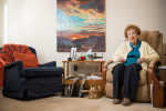 Doris Foster sits in an armchair in the living room of her unit at an independent living facility. The armchair next to her is empty.