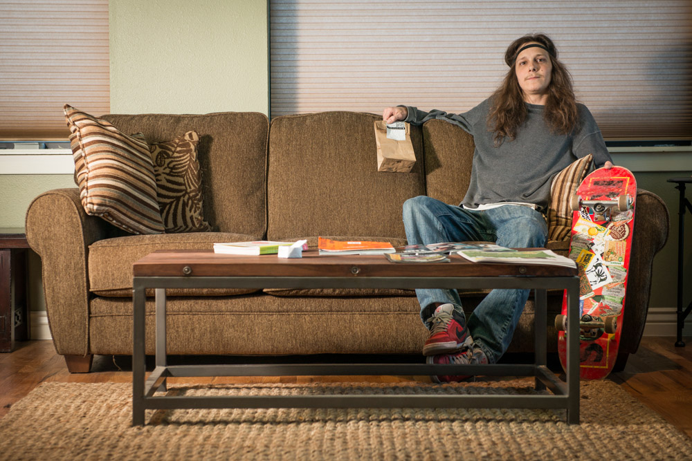 Ryan May sits on a couch in the Terrapin Dispensary waiting room while holding a brown paper bag containing the product from the dispensary. His skateboard sits beside him.