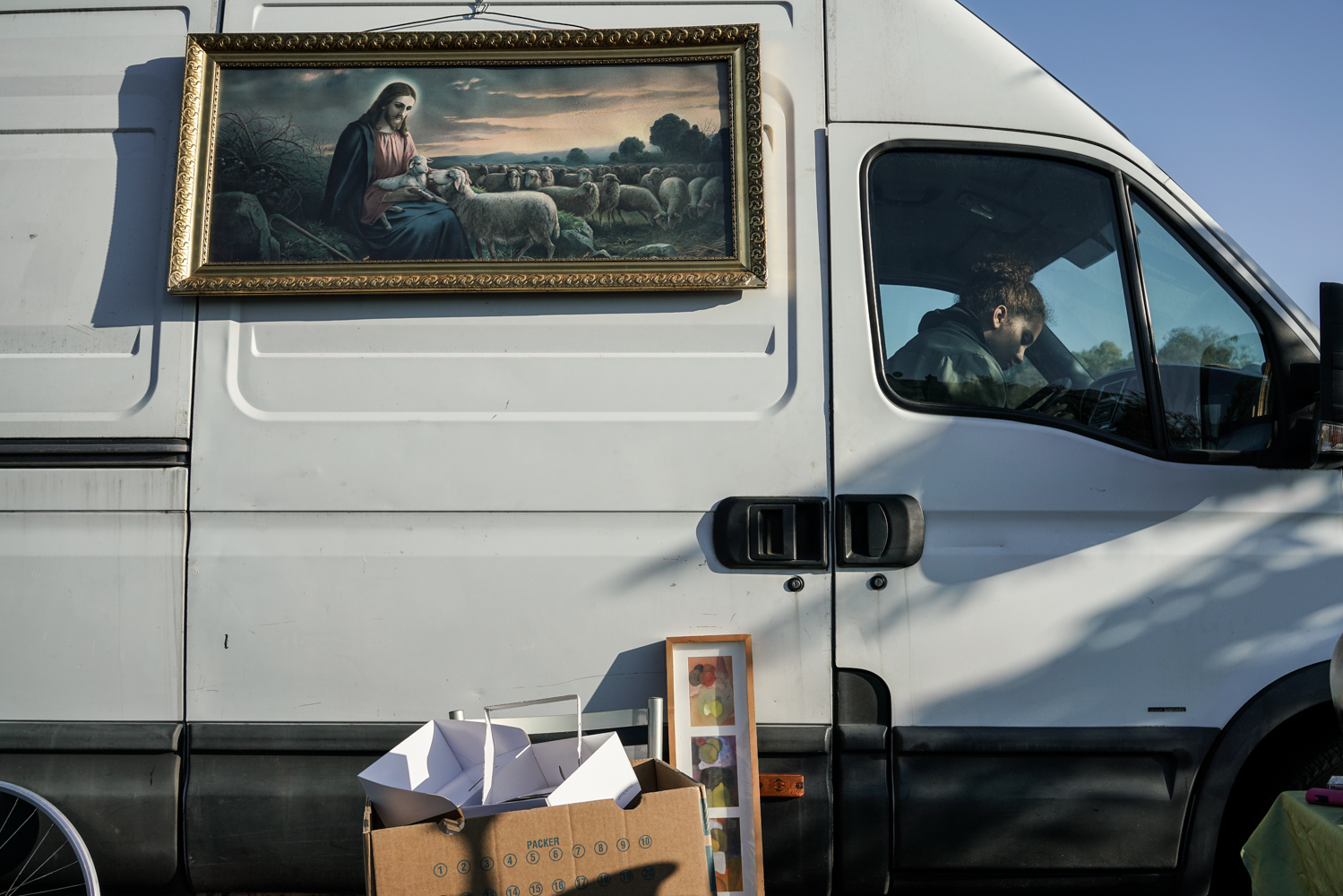 A girl is sitting in a van during a flea market in Offenbach