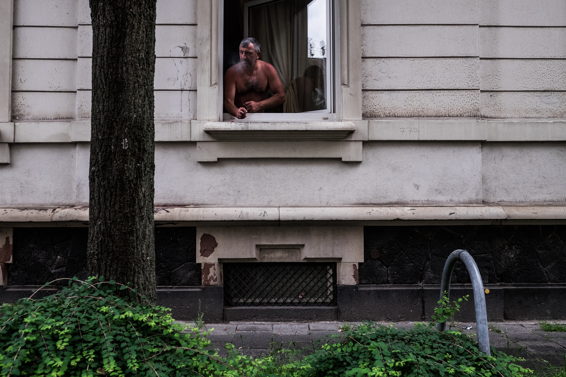 A man is staring out of his window in Offenbach