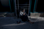 A homeless woman is sitting on the pavement in the evening sun in the Bahnhofsviertel district in Frankfurt in Germany