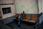 A man with a trumpet in his hands is sitting on a bench inside the central train station in Frankfurt in Germany