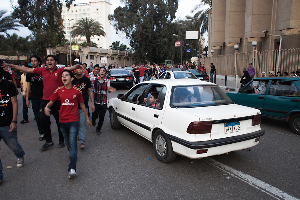 Members of the Ultras Ahlawy protesting next to the Ahly club centre in Zamalek/Cairo in April 2012. Young men are seen chanting while passersby watch.