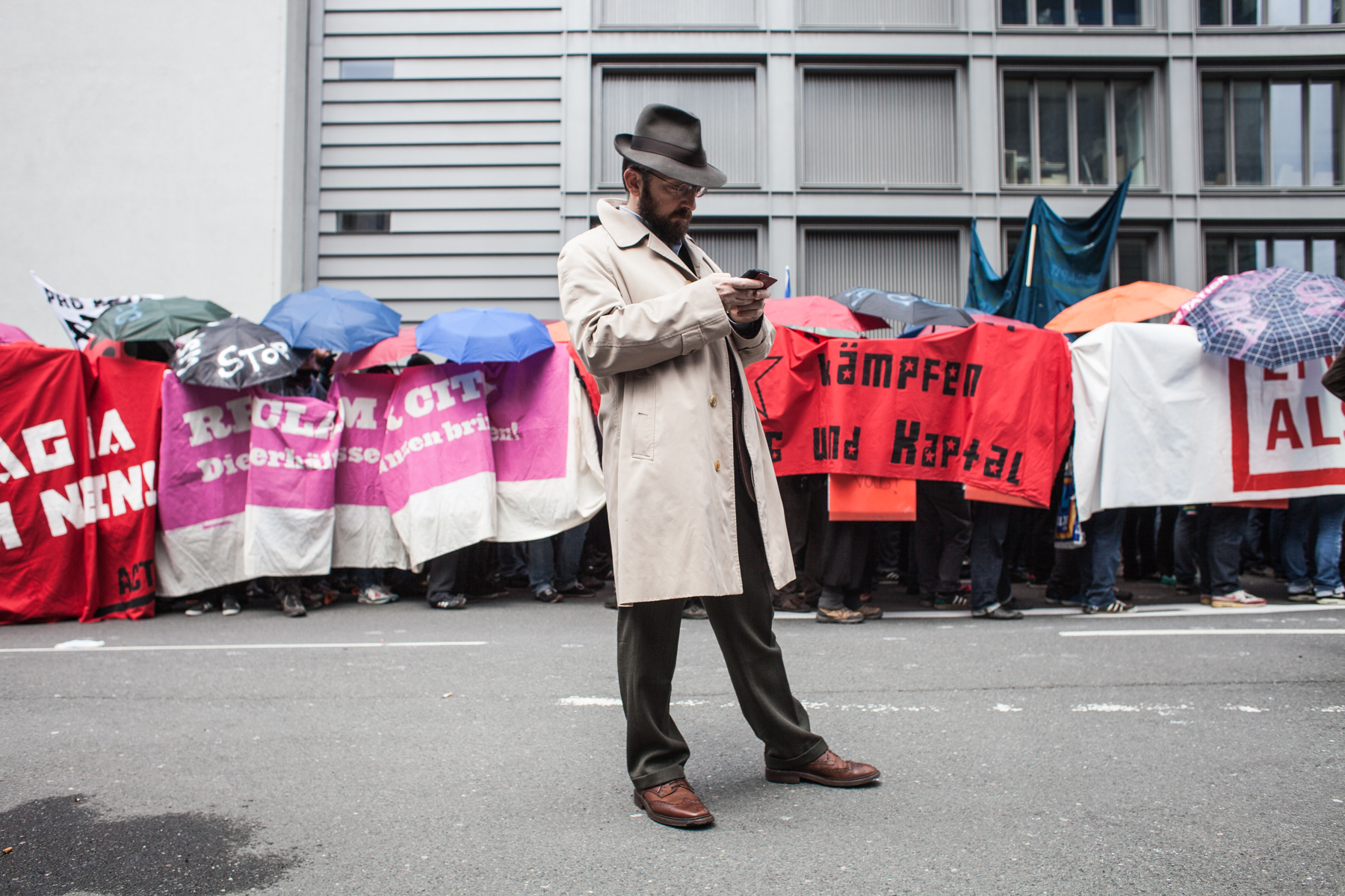 A man in a trench coat is checking his phone in front of left-wing protesters who are covered by banners and flags. Seen at the Blockupy protests in Frankfurt am Main in March 2013.