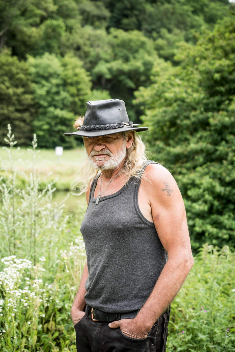 Claus, who lives in a tent next to the river Lahn in Germany, is standing close to the riverside.