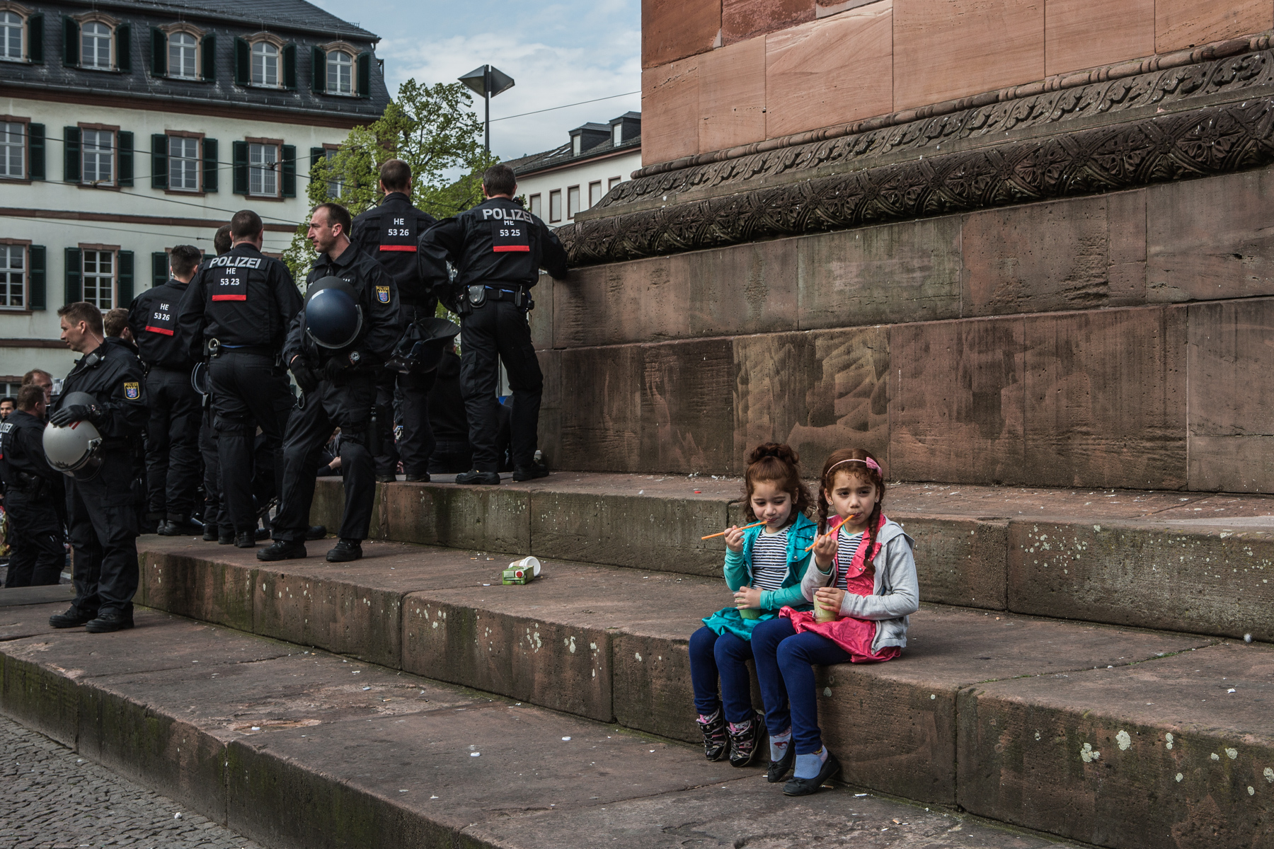 two little girls are sitting on the stairs leading to a monument and are eating icecream, Left to them a big group of police officers is standing