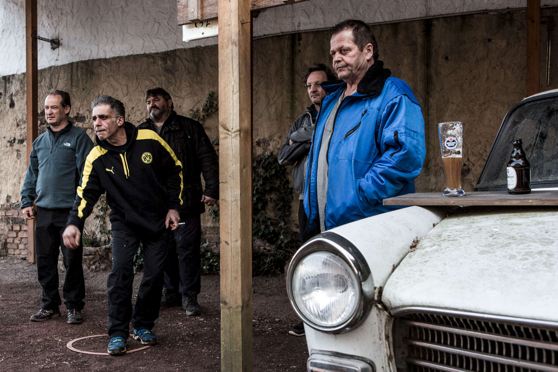 Men in the German Saar region are standing next to an old car and are playing the game Petanque