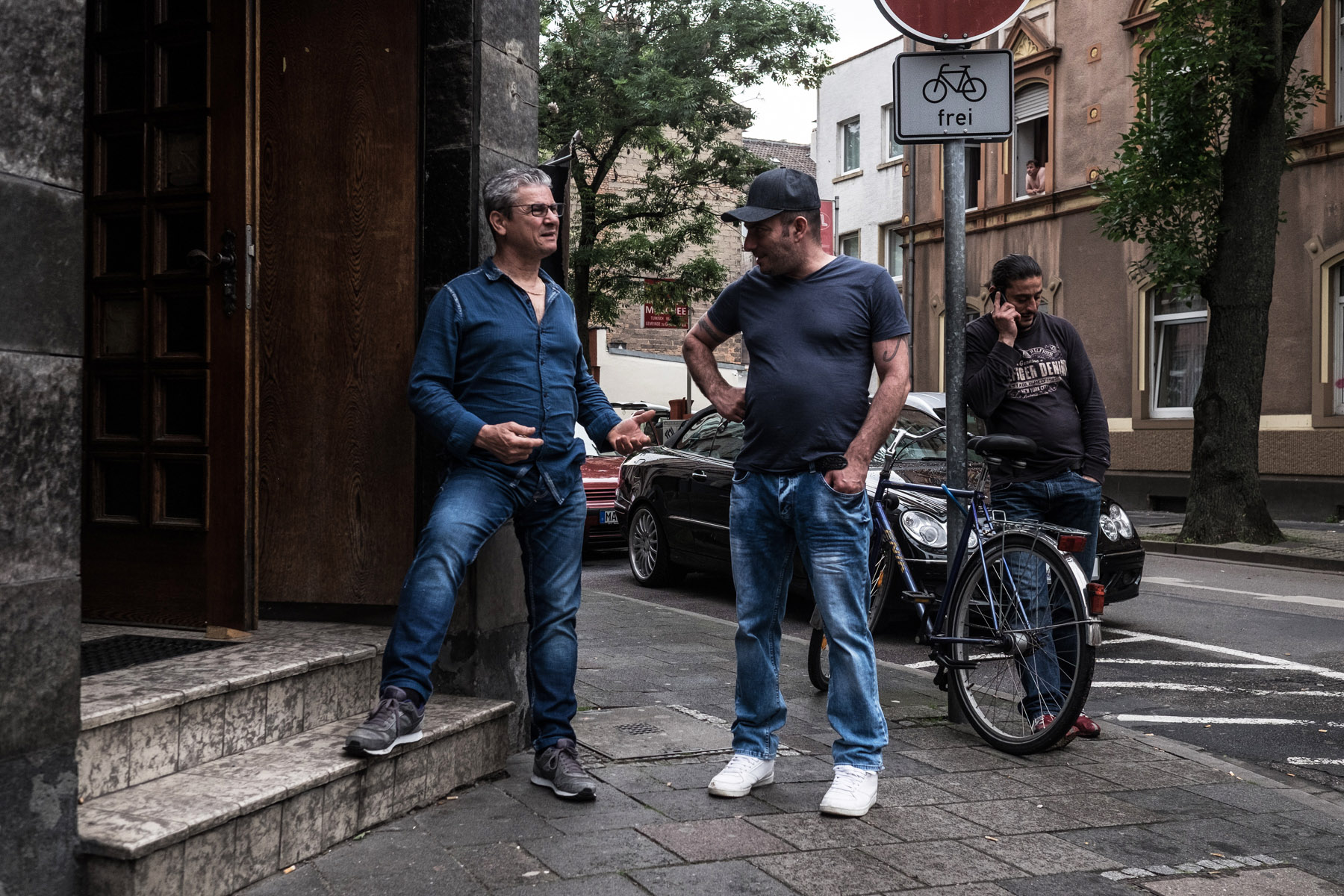 Two men are standing in front of an Italian pub in Offenbach's district Mathildenviertel while a third man is standing close behind them talking on his phone
