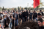 People are seen crying and lowering a casket into a freshly dug grave on a cemetary in the city of Diyarbakir. It is the burial of a female fighter of the Kurdish freedom movement PKK.