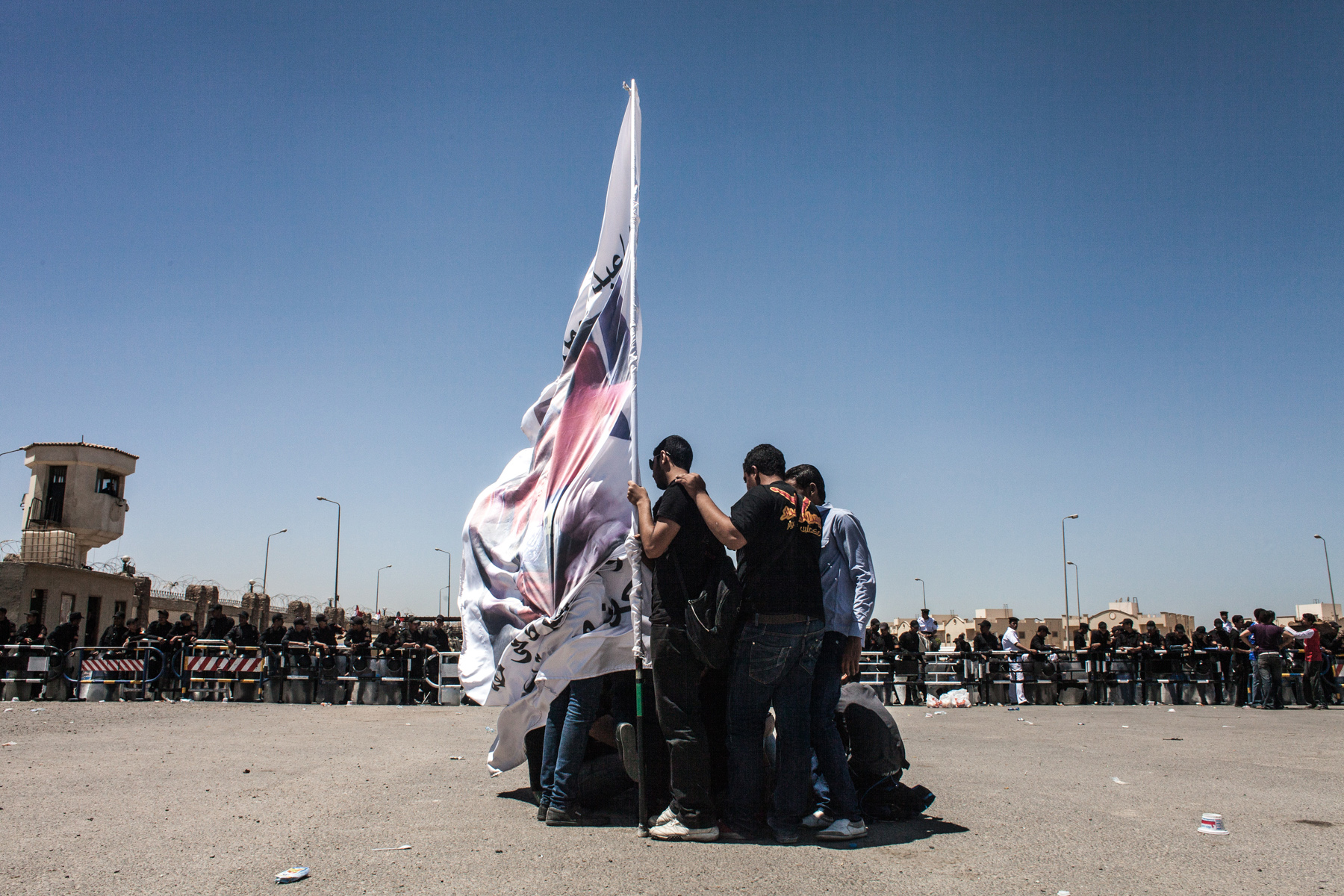 Ultras in front of the Police Academy in New Cairo where the Port Said trial is held. One member of the Ultras is seen holding a giant flag displaying faces of victims of the Port Said massacre