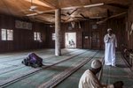 Muslim men are praying and sitting inside a mosque in Cameroon's capital Yaounde.