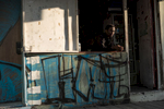 An African refugee is looking out of a ramshackle building near Lewinsky Park in Tel Aviv