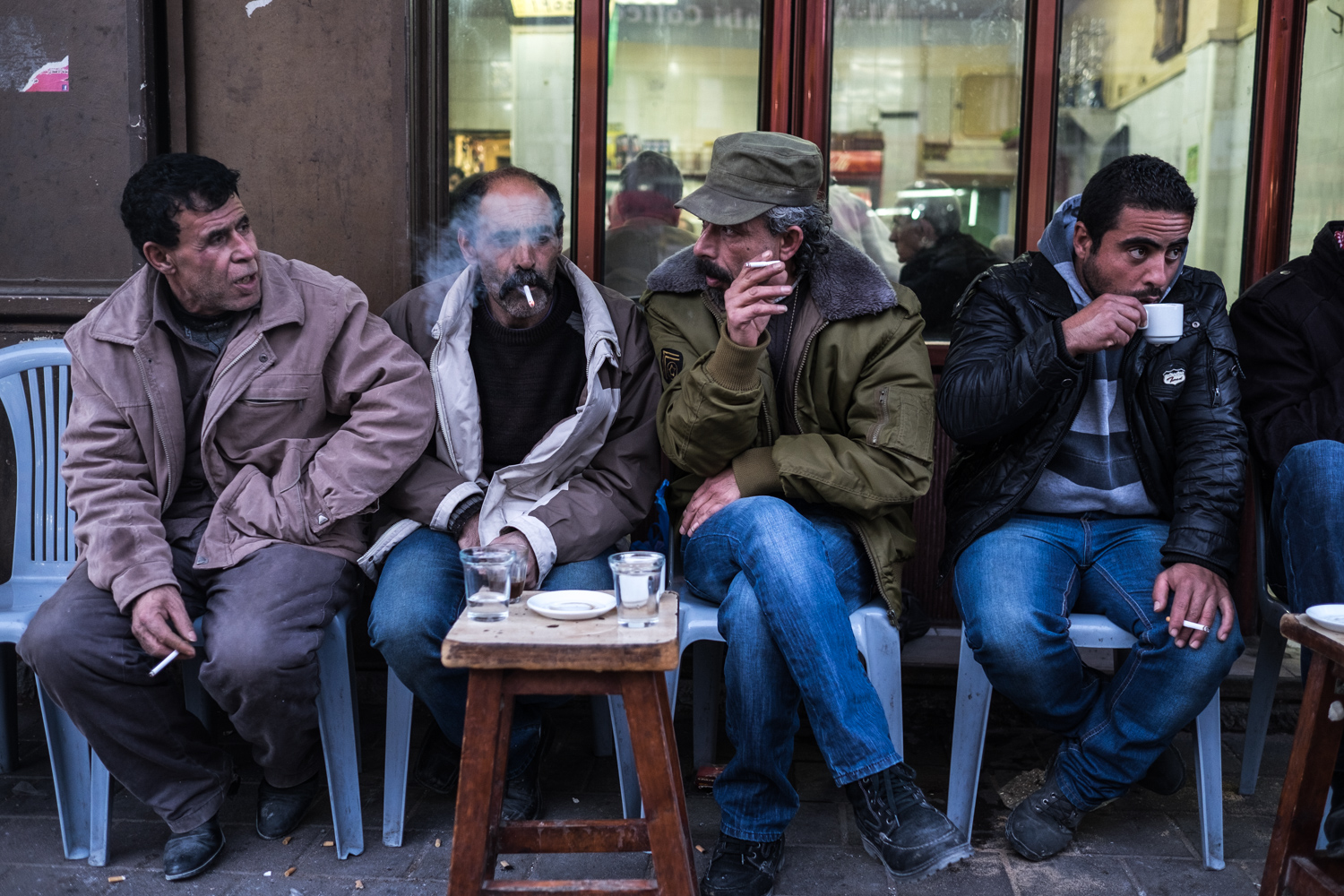 Men sitting in front of a café in Ramallah in the Westbank, smoking and having tea