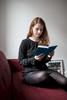 Dr. Judith von Heusinger sitzt in ihrer Wohnung in Frankfurt auf dem Sofa und liest ein Buch.
