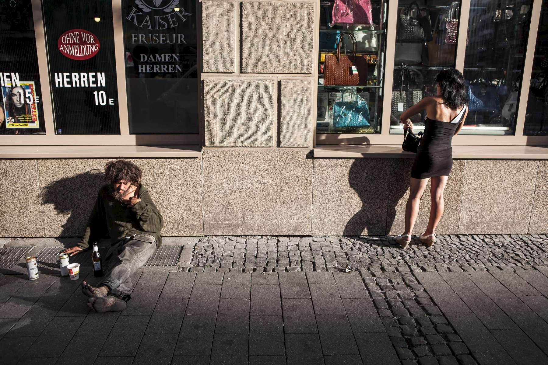homeless man sitting in front of shop windows while a woman is seen searching her bag close to Bahnhofsviertel in Frankfurt am Main in Germany