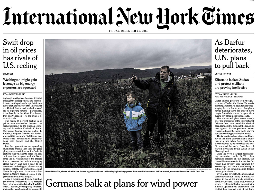 tearsheet of fronpage of International New York Times showing Harald Hossfeld with his son in a field in the state of Hesse in Germany. Hossfeld leads a protest movement against wind power in the area.