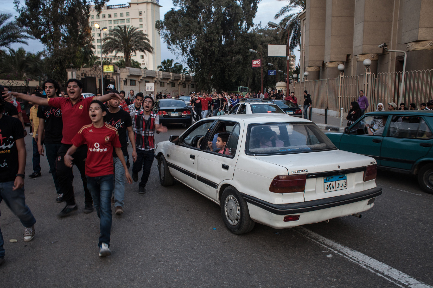 Ultras protesting next to the Ahly club centre in Zamalek/Cairo while a young boy is watching them out of his parents car