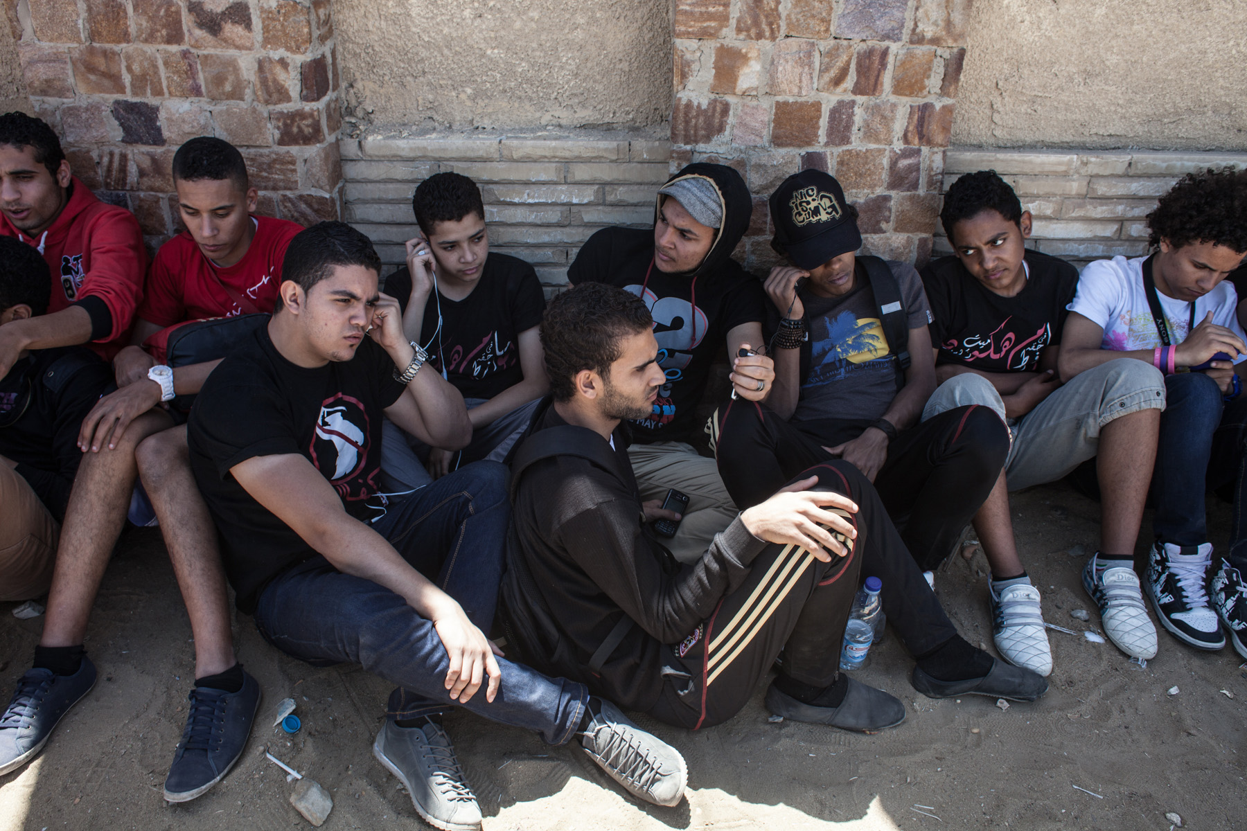 a group of Ultras is sitting next to a wall in front of the Police Academy in New Cairo where the Port Said trial is held