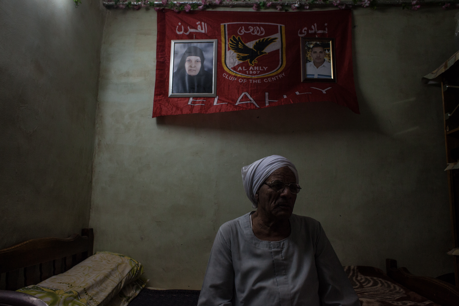 father of Ultra Youssef who died in Port Said. He is sitting in front of a Al-Ahly flag and pictures of his deceased wife and son