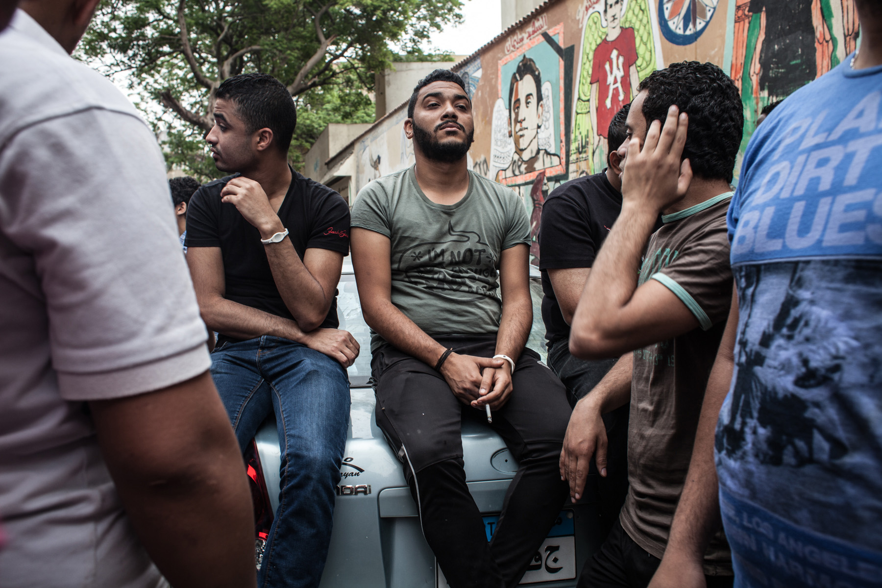 Tika, founding member of the Ahlawy, is sitting on a car close to Tahrir Square in the famous Mohammed Mahmoud street in Cairo while being surrounded by other members of the Ahlawy