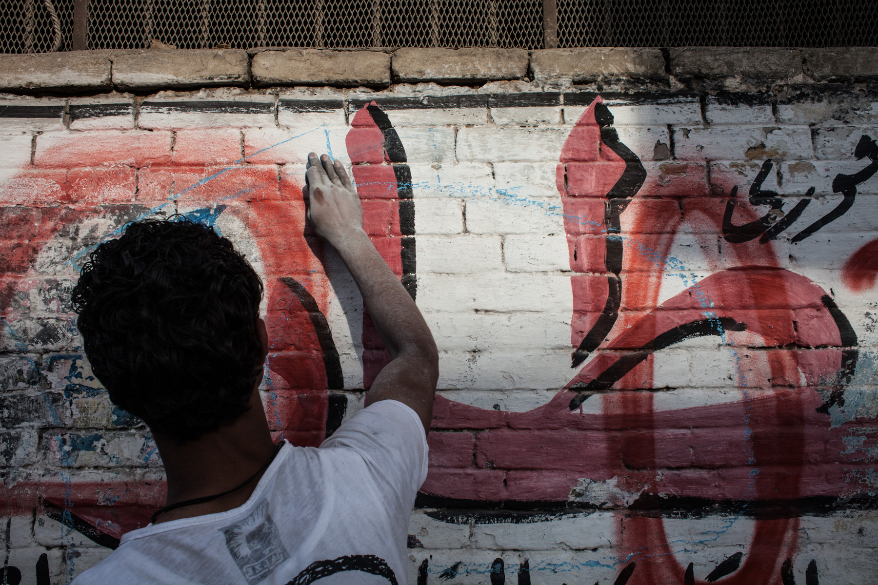 a member of the Ahlawy drawing illegal wall paintings in Cairo's district Matereya.