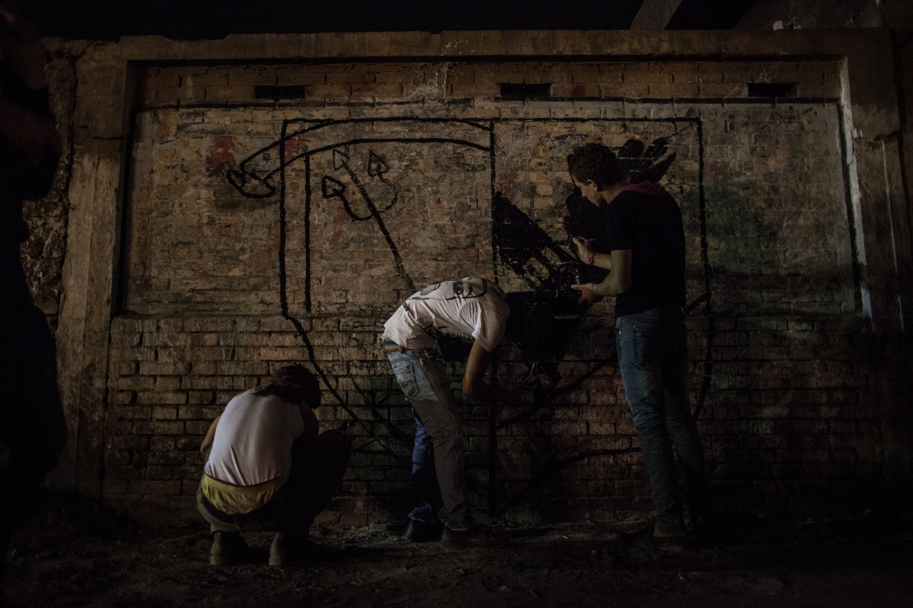 Ahlawy drawing illegal paintings on a wall in Cairo's district Matereya