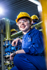 Environmental portrait of young apprentice at work. Woman with a hard hat in a factory