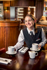 Environmental portrait of young apprentice waiter working in hospitality. woman serving coffee in a hotel.