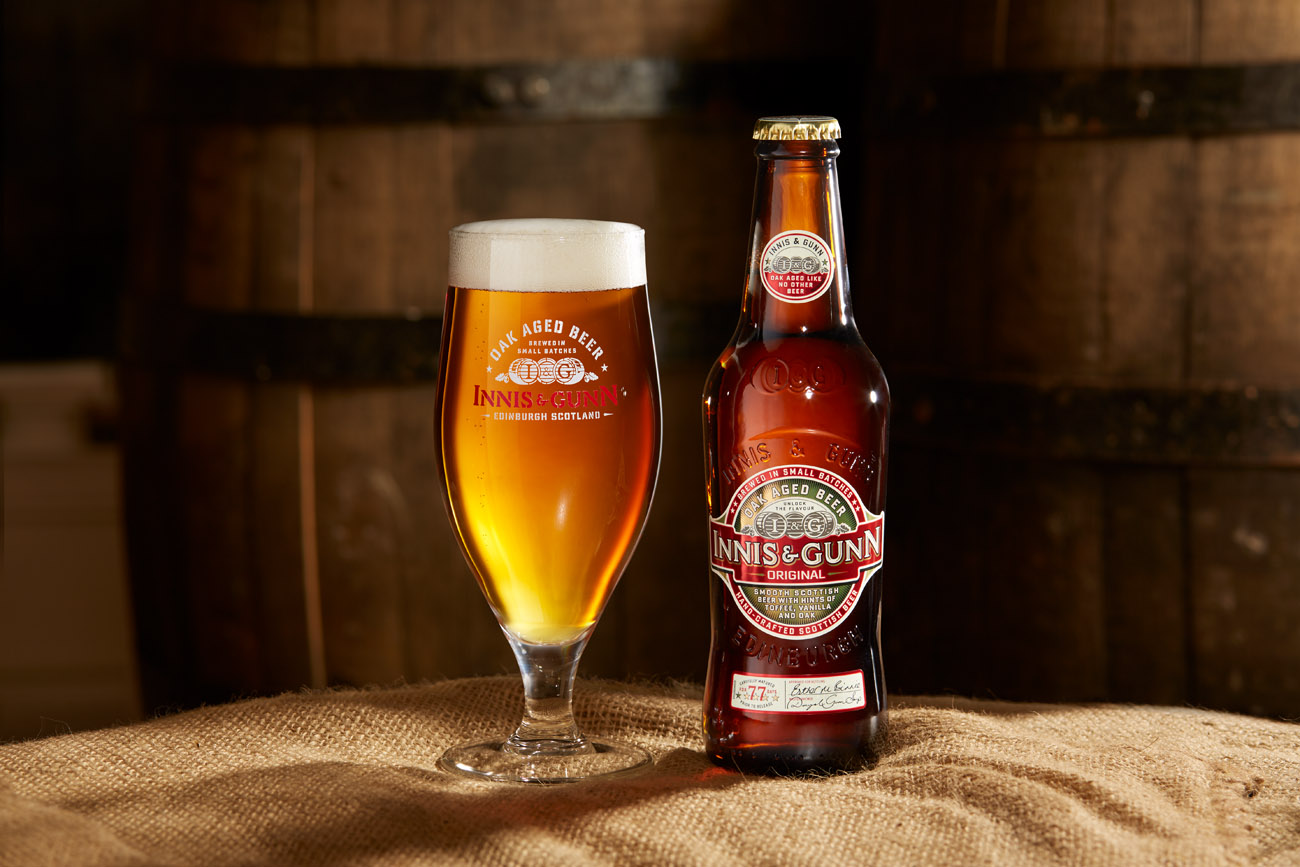 bottle and glass of Innis and Gunn original sitting on a barrel in a warehouse with barrells behind. Drinks photography