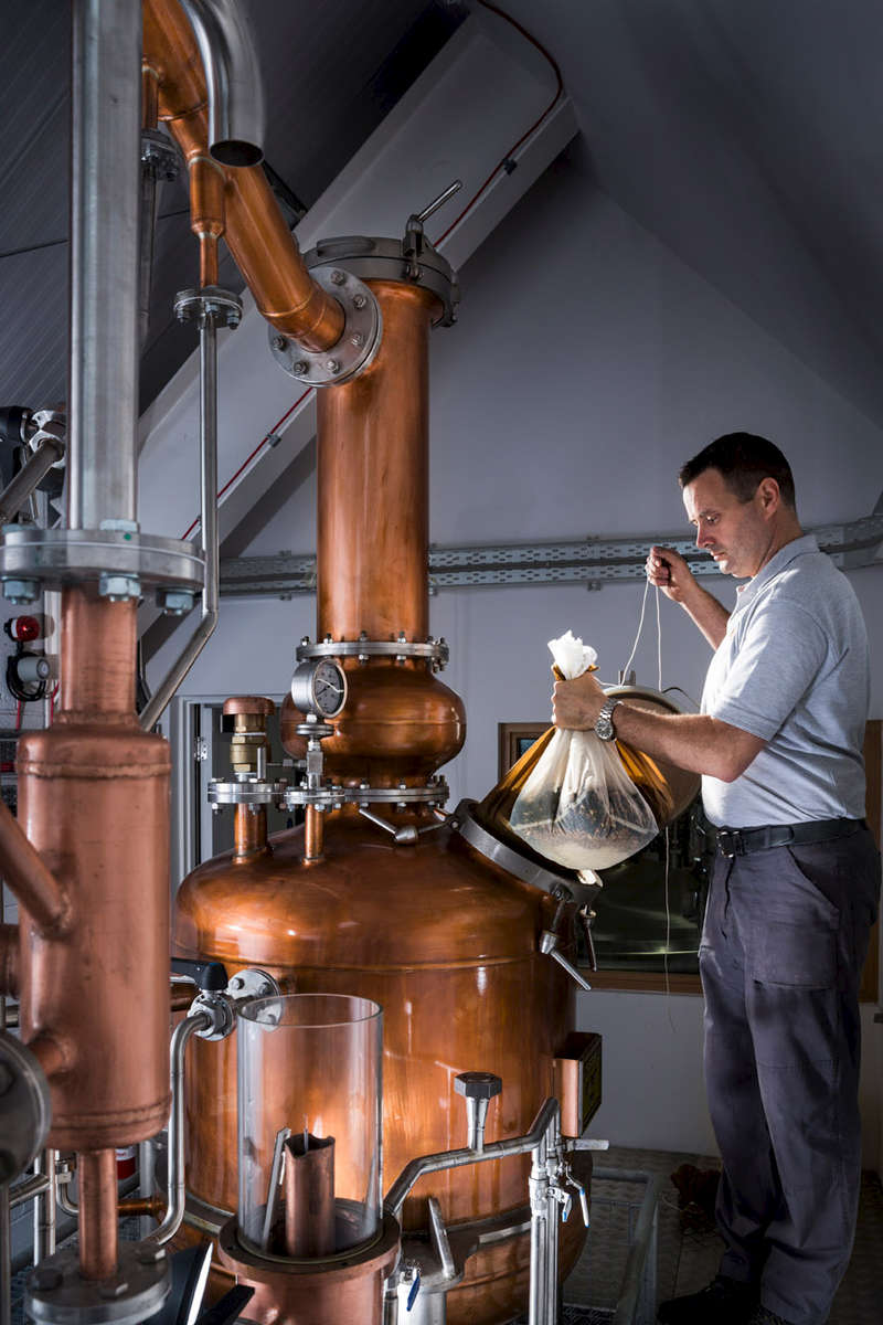 Gin still being loaded with botanicals