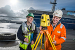 Environmental portrait of young apprentice at work with a theodolite at a harbour pier. young man with a mentor.