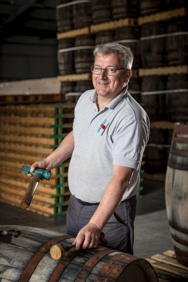 smiling distiller removing a bung from a cask in a warehouse