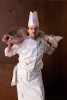 a chef in whites holds a giant bloody fish around his shoulders.