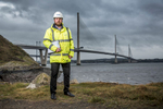 Environmental portrait of young apprentice at work beside queensferry crossing,